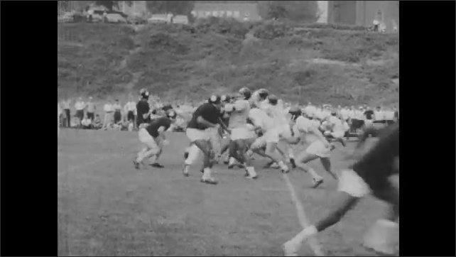 1960s: Players practice football scrimmage on field. Players run across field and toward a tackle.