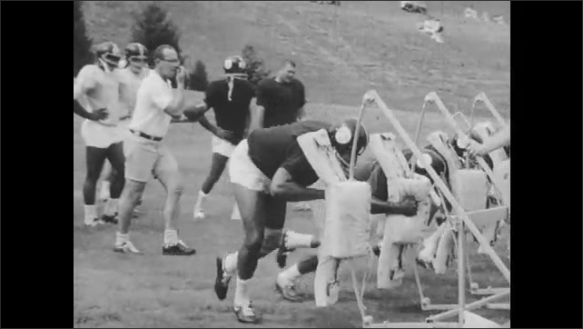 1960s: In slow-motion, players lunge into tackle on wooden frame impact equipment as coach stands on wood and players move the frame down field.