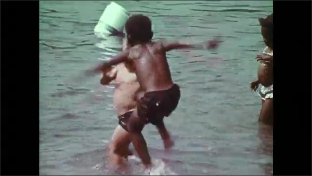 1970s: Children wrestle and splash in shallow pool. Man oversees children in shallow pool. Boys splash one another.