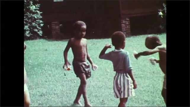 1970s: Child dumps cup of sand on boy's head. Children play around sand pit. Boy dumps cups of sand on boy's head. Children play at sand pit. Children pour water and play in kiddie pools.