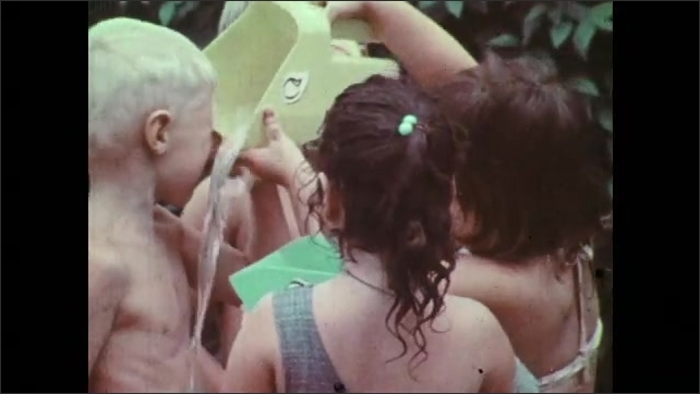 1970s: Children pour water and play in kiddie pools. Boy blows water from hose and funnel. Boy sprays hose on children at kiddie pools.