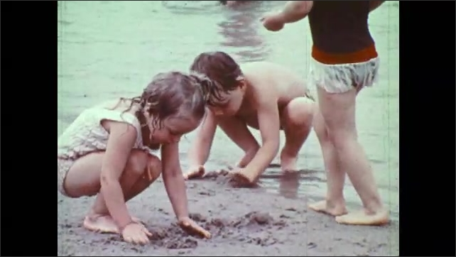 1970s: Girls and boy scoop sand at lake shore. Girls talk to each other. Boys and girls splash and play in shallow lake.