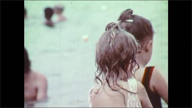 1970s: Girls talk and nod. Girl walks into lake.  Boys and girls splash and play in shallow lake.