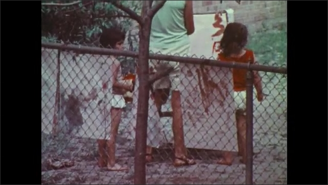 1970s: Girl runs around playground with toy car. Girl runs into sand pit.