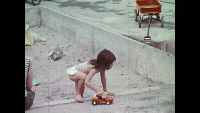 1970s: Woman sits in sand pit near girl. Girl carries toy car around playground. Girl shows car to children near kiddie pools.