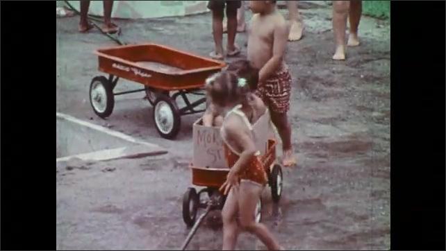 1970s: Girl pulls boy in box on wagon. Girl pulls wagon around playground. Girl picks up toy car and hands it to boy on wagon. Children pull wagons around playground.