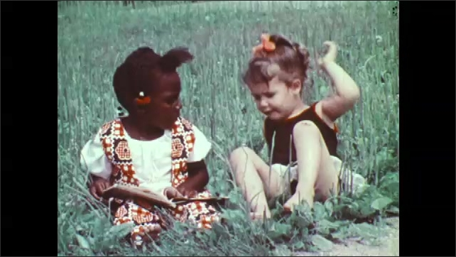 1970s: Girls sit in grass and read books, Girls read books and talk. Children play around girls reading in grass.