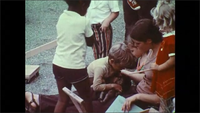1970s: Children gather around woman with book. Boy grabs at book. Woman scolds boy. Girl hits boy in head. Boy lays on lap of woman. Woman reads book to boy.