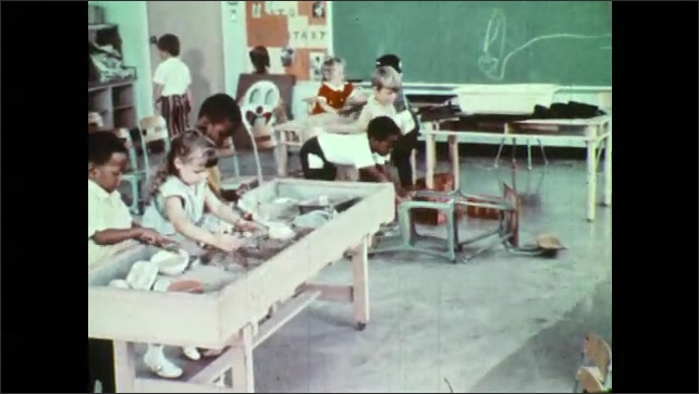 1970s: Boys turn chairs over and push them against each other. Boy wanders toward sand table.