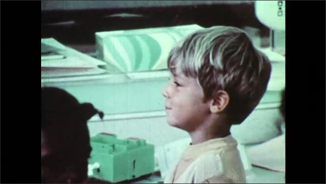 1970s: Boy walks through classroom and cries. Woman kneels and consoles crying child. Boy picks up toy from shelf and throws it at girl.