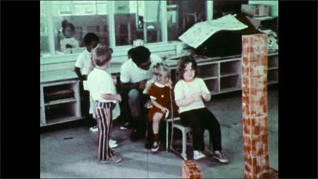 1970s: Man and children sit on chairs and pretend. Children watch teacher and children on chairs.