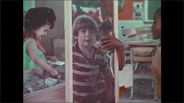 1970s: Children play dress up and don hats in front of mirror. Boy looks at self in mirror. Boys and girls wear hats.