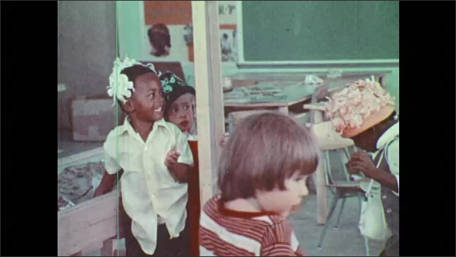 1970s: Children play dress up and don hats in front of mirror. Boys and girls wear hats and smile.