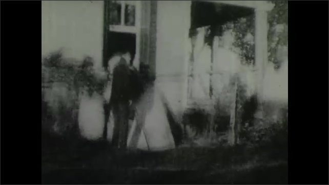 1900s: Woman steps out of window onto barrel as man riding horse pulls up next to her. Woman climbs onto back of horse. Man follows woman out window as man closes window on him, they fight on ground.