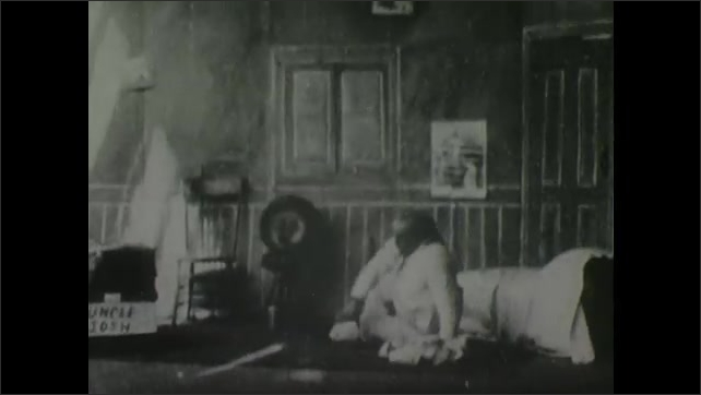 1900s: Man lays in bed as woman stands next to him. Woman leaves room. Man in black appears and takes bed covers off man laying down. They fight over covers. Man disappears and reappears.