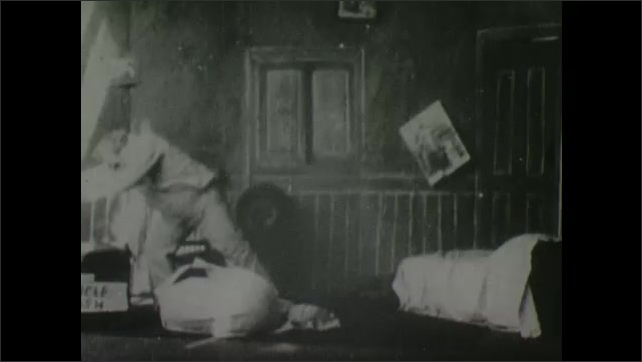 1900s: Man ties up other man in sheets on ground. Man picks wrapped man up and places him in trunk.