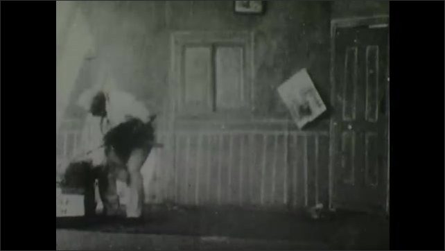 1900s: Man on floor in empty bedroom stands up, looks around then opens trunk with man inside. Man in trunk stands up and furniture appears in bedroom.