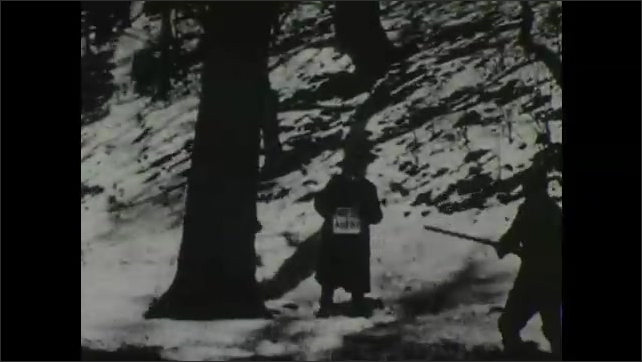 1900s: Man runs down hillside followed by two people with signs. Man holds up gun to tree, fires and animal falls from it as two men with signs watch.