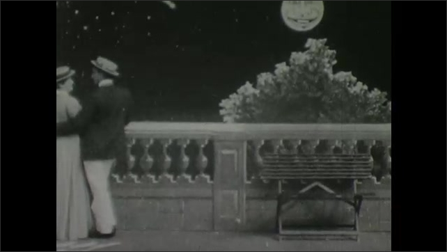 1900s: Man and woman walk onto terrace together. They embrace. The moon grows a face and smiles at them. They sit down and the moon frowns.