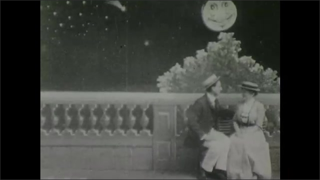 1900s: Man woman sit together on bench. Moon behind them makes faces then leers down on them. Woman faints into man's arms. Man fans woman.