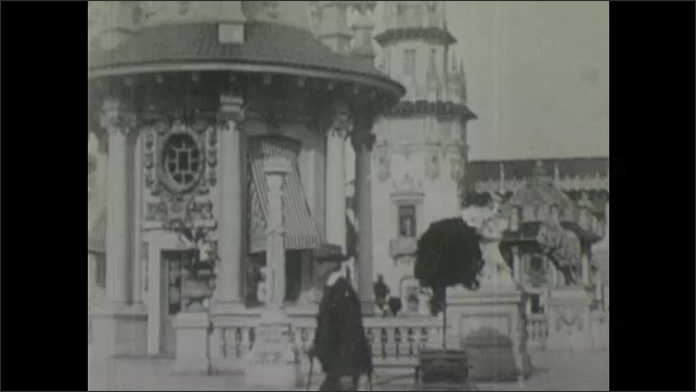 1900s: People walk around courtyard with stone pillars, benches and buildings.