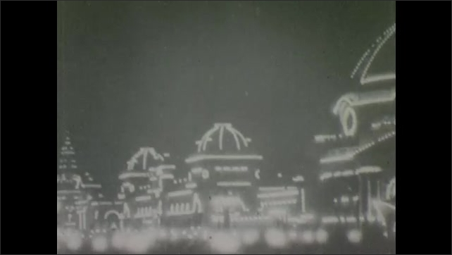 1900s: Buildings around city courtyard are lit up at night, lined with lights.