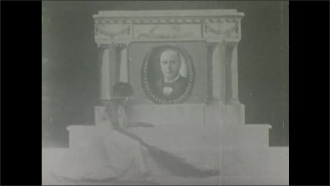 1900s: Woman kneels in front of memorial with picture of William McKinley on it.