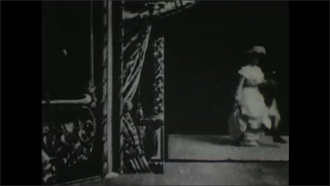 1900s: Man in theater watches projection of woman dancing. Man begins dancing in front of screen with woman on screen.