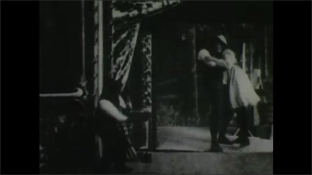 1900s: Man stands in front of movie screen in theater and reacts to projection of man being injured while pumping water from well. Man tears screen down and rolls on ground.