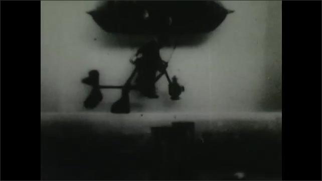 1900s: Man rides blimp in sky by peddling wheels underneath blimp.