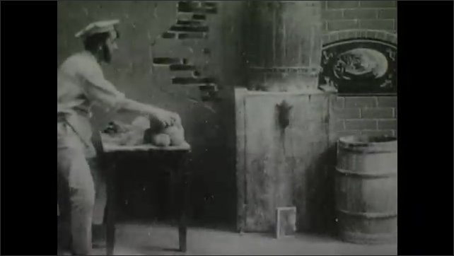 1900s: Man in kitchen begins rolling dough when rat climbs up wall. Man throws dough onto rat on wall, then shapes dough into face of smiling man.