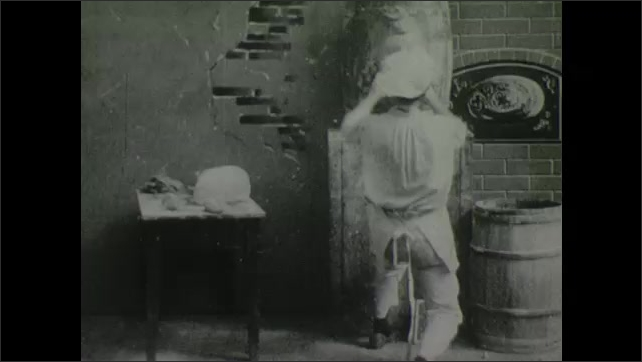 1900s: Man in kitchen shows face made of dough on wall to other man. Then man throws dough into other man's face. Then he throws dough onto face made of dough and reshapes new face.