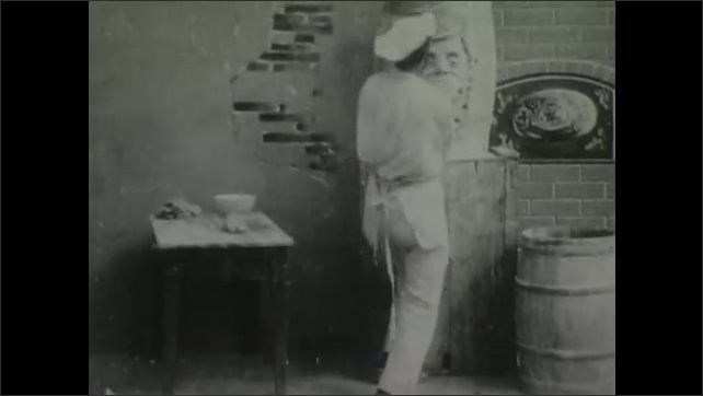 1900s: Man in kitchen crafts face out of dough on wall. Two men enter kitchen and dump man into barrel of flour.