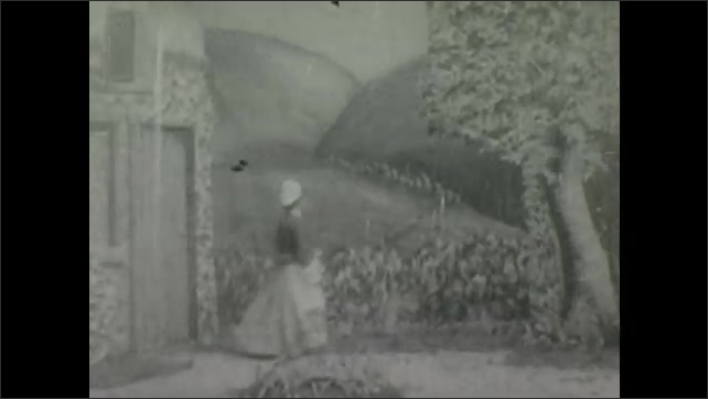 1900s: Theater, waterfall, man pushes people in cow costume, they cross bridge. Woman walks through door, gestures, person sprinkles something from hat, woman grabs hat, turns hat over.
