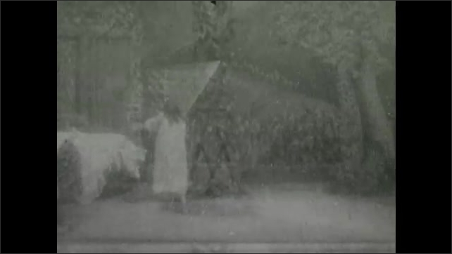 1900s: Theater, egg pops out of hole, grows, cracks, person appears. Sleeping girl wakes, gets out of bed, walks to window. Woman, child walk out door, gesture, look up.
