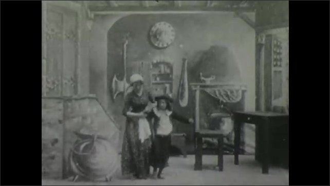 1900s: Theater, woman cleans table with rag, opens door, welcomes child in, they gesture, hold hands, spin, woman puts child in urn. Soldier marches in with gun, sits.