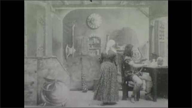 1900s: Theater, soldier sits at table, stands, gestures, sits, woman scurries around, brings out lyre. Boy pops out of urn, points, gestures to sleep.
