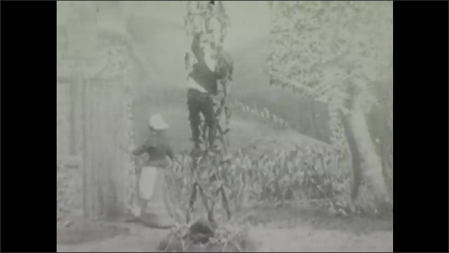 1900s: Theater, outdoors, woman walks around tall structure, waves hands, looks worried, beckons, gestures, boy climbs down. Boy chops base of structure with ax, structure falls down.
