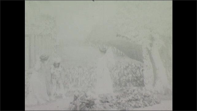 1900s: Theater, outdoors, woman shields boy, man writhes on ground, long rope falls from sky, angel with wings and wand appears.