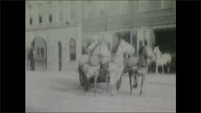 1900s: Firemen leave firehouse in horse drawn wagons, rush past crowd of people standing by road.