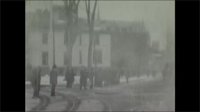 1900s: Crowd of people stand by road, watch firemen rush past in horse drawn wagons.
