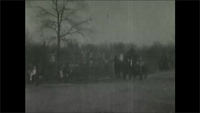 1900s: Crowd of people stand by road, watch firemen rush past in horse drawn wagons.  Firemen unroll hose in front of houses.