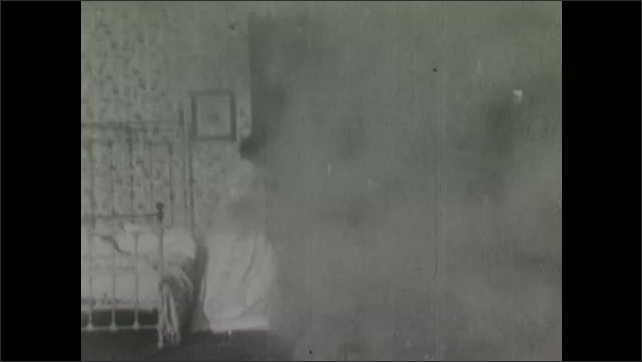 1900s: Firemen unroll hose in front of houses. Smoke billows into bedroom, woman wakes, stretches, waves arms, holds head in hands, looks out window, collapses onto bed.