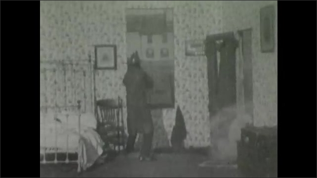 1900s: Smoke billows into bedroom, woman lies collapsed on bed, fireman rushes in, rips curtains down, breaks out window with axe, throws woman over shoulder, climbs out window.