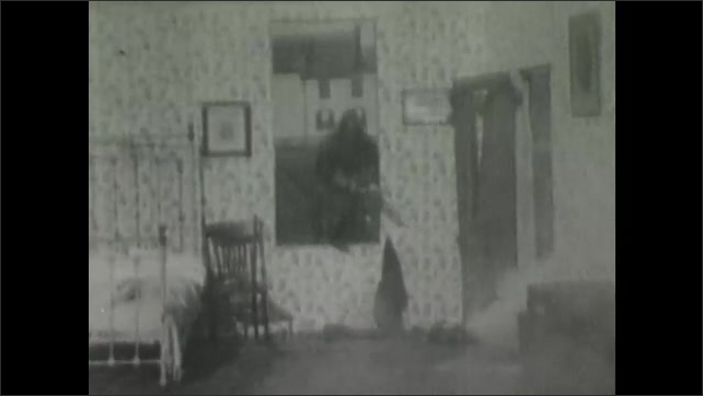 1900s: Smoke billows into bedroom, fireman climbs in through window, picks up child lying on bed, carries child out. Firemen climb through window with hose, spray water.
