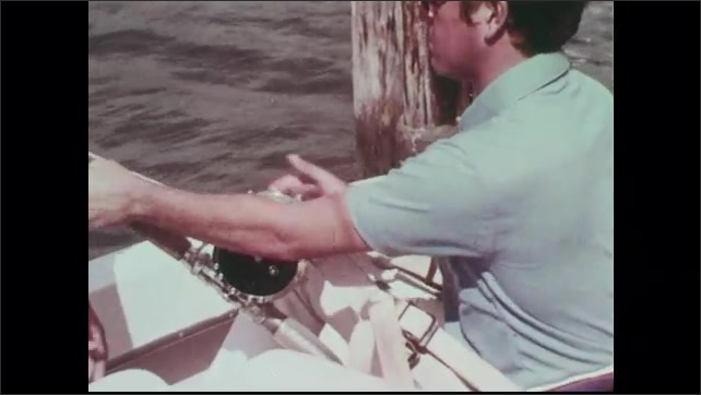 1960s: Man puts fish on hook for bait. Tourist straps into fighting chair on deck of charter fishing boat by a worker.