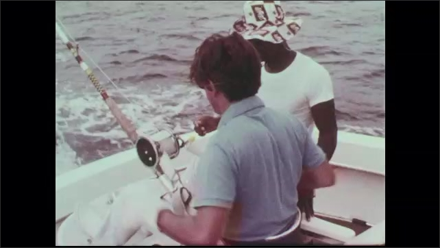 1960s: Wake of boat. Fisherman puts on safety gloves next to fighting chair. Man fishes off of boat.