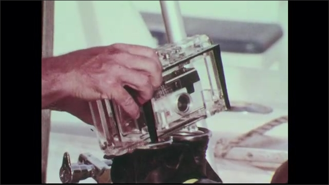 1960s: Camera in Dacor underwater housing. Scuba diver points camera at horizon. Deckhand in Schlitz hat smiles.