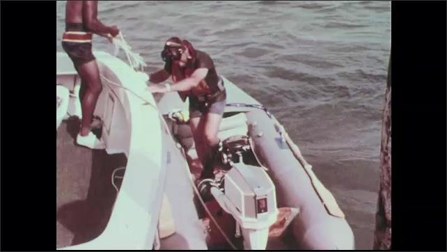 1960s: Scuba diver loads equipment into dinghy. Deckhand comes aboard dinghy as scuba diver starts outboard motor.
