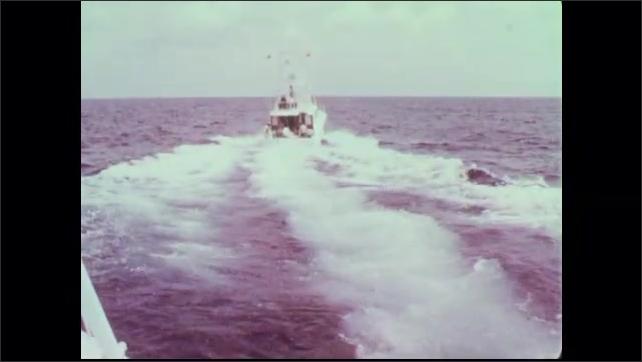 1960s: Captain pilots boat. Fishing boat speeds leaving wake.